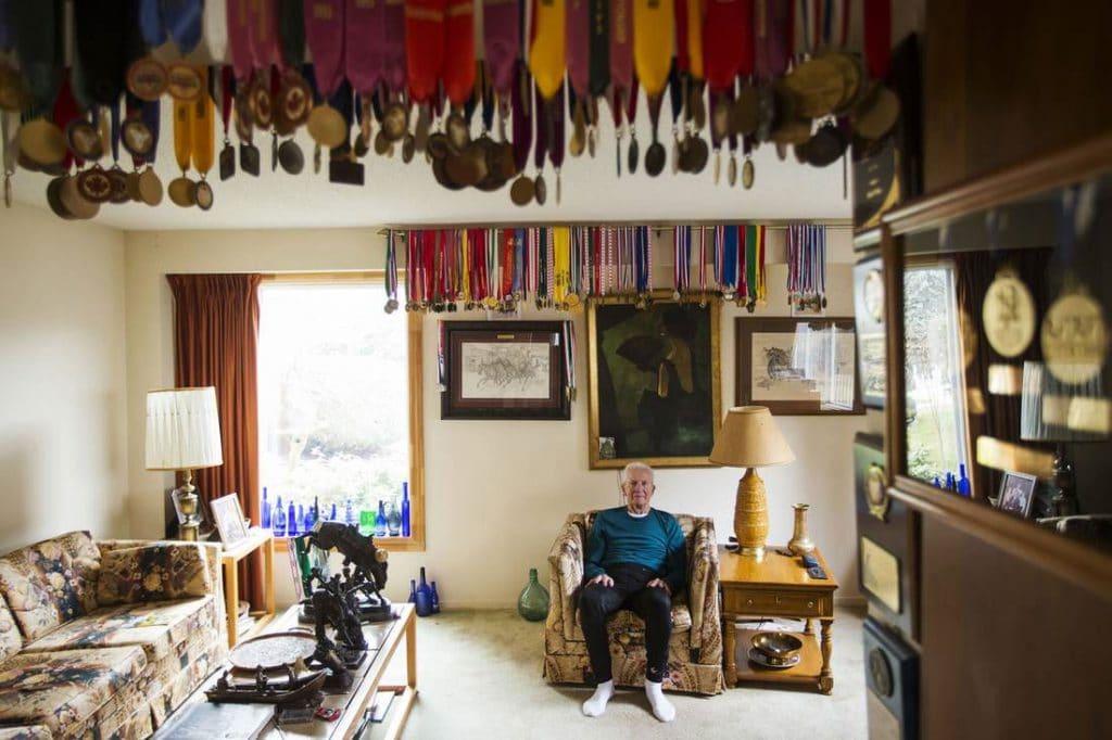 Earl Fee in zijn woonkamer, te midden van zijn mooiste medailles (foto Mark Blinch, social media)